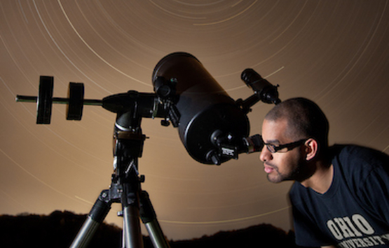 A student looks into a telescope