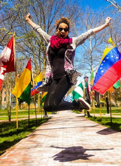 International Week participant jumping in front of a row of international flags.
